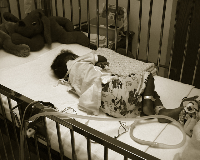 Sick baby in cot with tubes