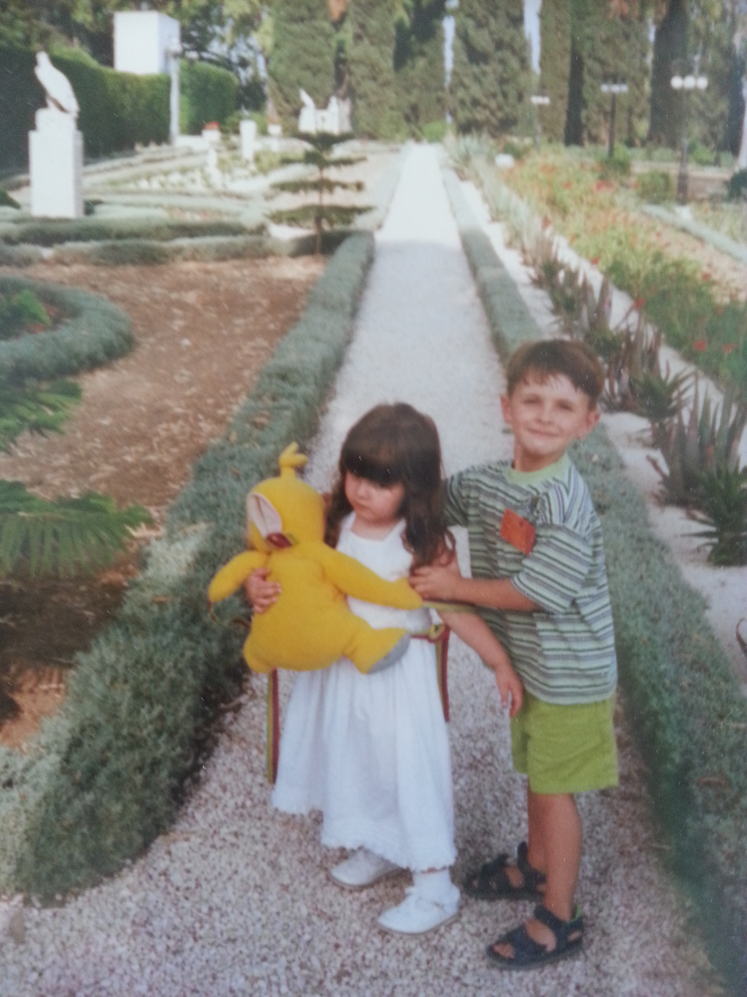 Farrah holding Lala (Teletubbie) with her brother trying to get her to look and smile at the camera in the gardens of Baha'u'llah in Akka, Israel